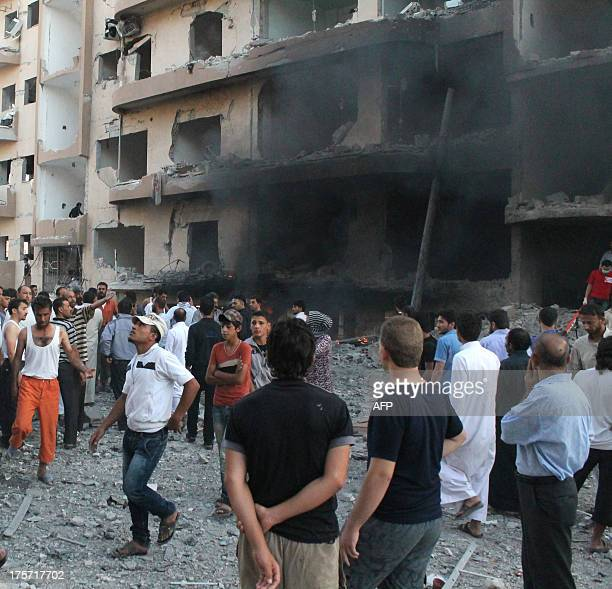 People gather at the scene of an explosion in the northern Syrian city of Raqqa early on August 7 2013 UN weapons inspectors tasked with looking into...