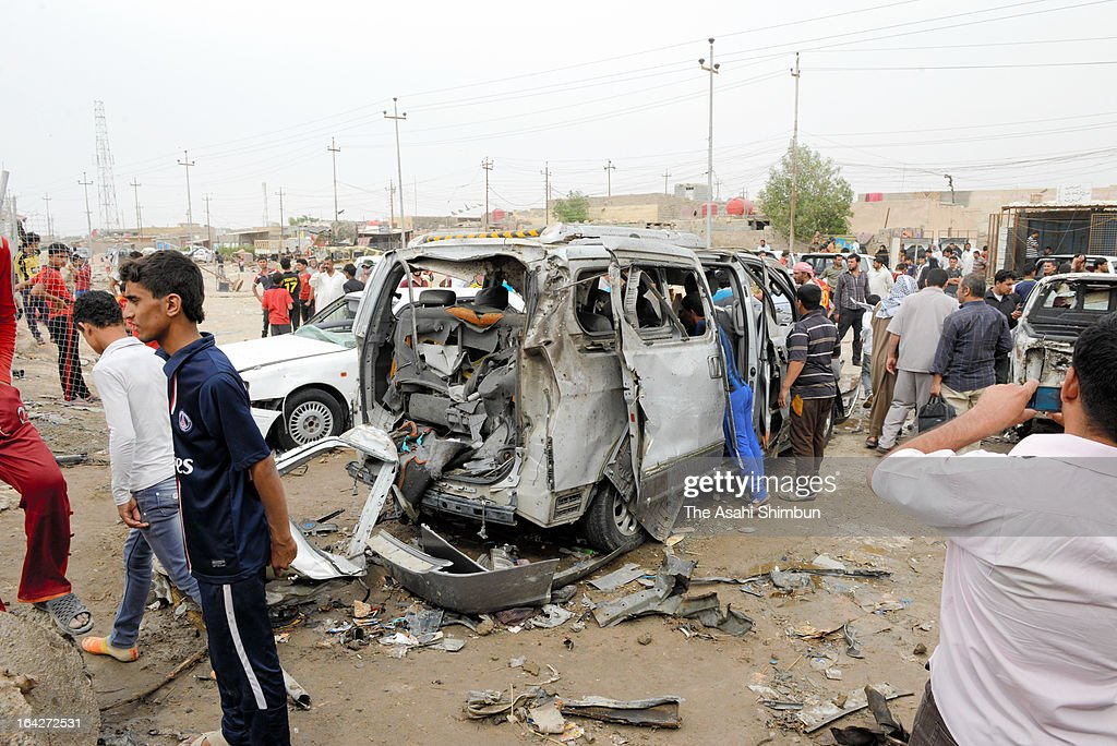 People gather at the site of a car bomb blast on March 17, 2013 near the city of Basra, Iraq.