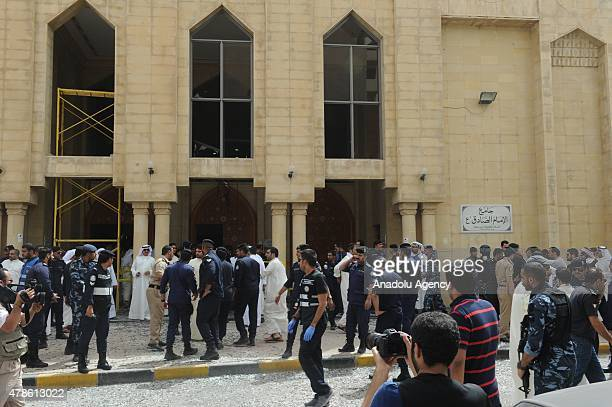 People gather at the site of a suicide bomb attack targeting the Imam Sadiq Mosque in the Sawaber area of Kuwait City on June 26 2015 Ten people were...