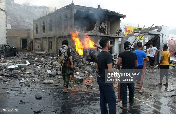 People gather at the site of a suicide car bombing outside Yemen's presidential palace in the city of Aden on January 28 2016 Islamic State jihadist...