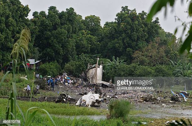 People gather at the site where a cargo plane crashed into a small farming community on a small island in the White Nile river close to Juba airport...