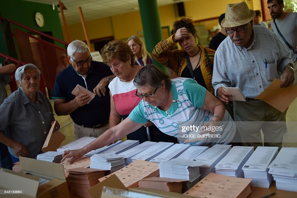 people gather ballots sheets to vote in Spains general election at the Bernadette college polling station in Moncloa-Aravaca, Madrid, on June 26, 2016. Spain votes today, six months after an inconclusive election which saw parties unable to agree on a coalition government. GUERRERO