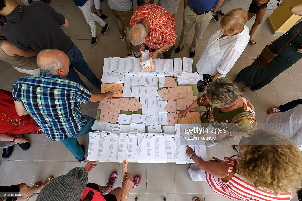 people gather ballots sheets to vote in Spains general election at the Bernadette college polling station in Moncloa-Aravaca, Madrid, on June 26, 2016. Spain votes today, six months after an inconclusive election which saw parties unable to agree on a coalition government. MANSO
