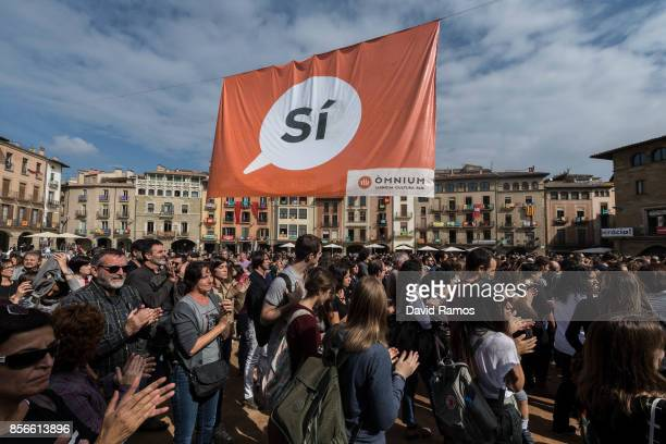 People gather beneath a large banner where it reads 'Si' 'Yes' in Catalan during a protest against the violence that marred yesterday's referendum...