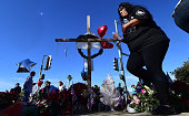 People gather beside a makeshift shrine to the victims of last week's shooting attack December 7 2015 in San Bernardino California The husband and...
