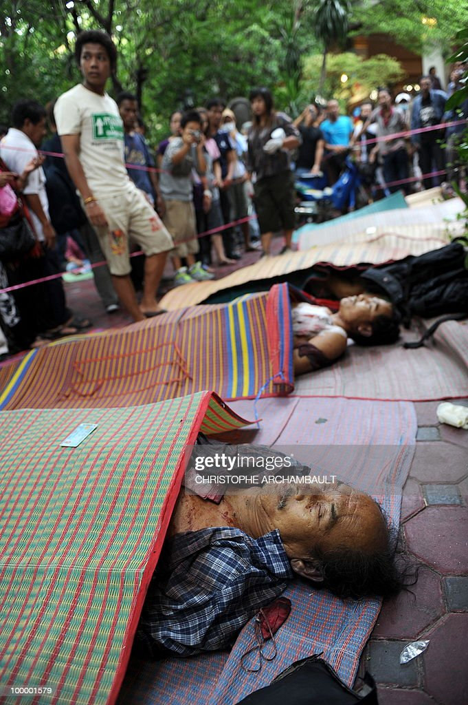 People gather beside the dead bodies of anti-government protesters killed in a gunbattle the day before at a temple which had been turned into a shelter within an anti-government protest site in downtown Bangkok on May 20, 2010. Gunshots rang out near a Buddhist temple in the heart of an anti-government protest zone in Bangkok, and soldiers were advancing on foot along an elevated train track, an AFP photographer saw. Thai security forces stormed the 'Red Shirts' protest camp on May 19 in a bloody assault that forced the surrender of the movement's leaders who asked their supporters to disperse. AFP PHOTO/Christophe ARCHAMBAULT