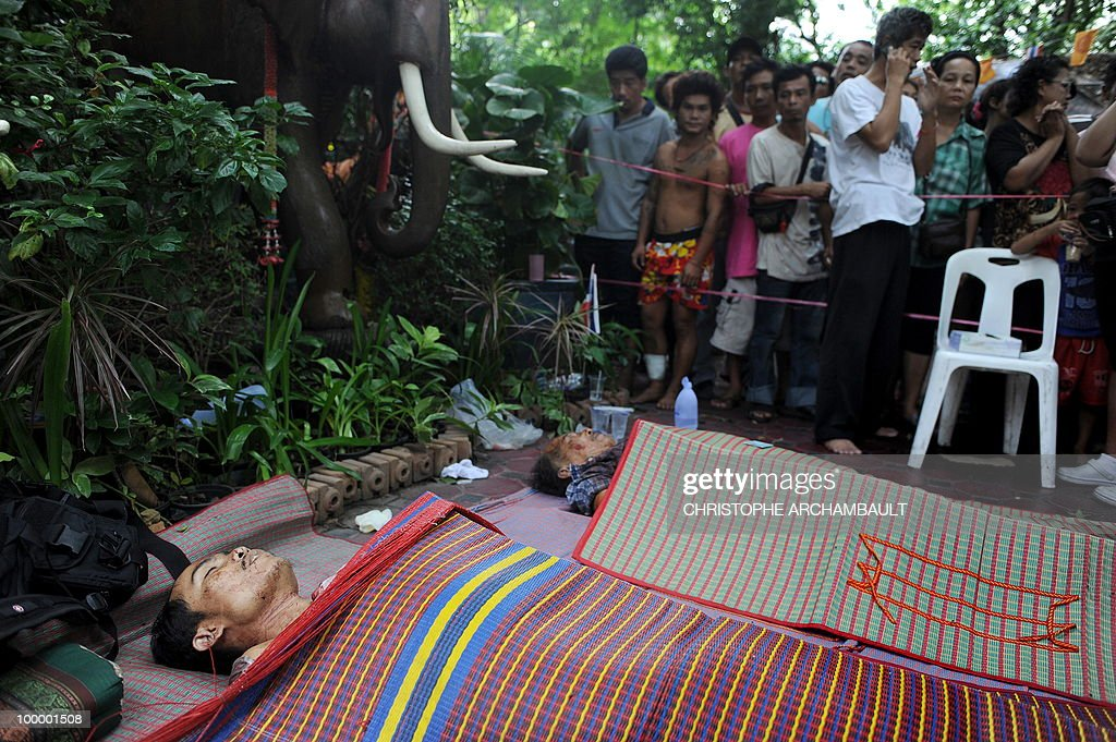 People gather beside the dead bodies of anti-government protestors killed in a gunbattle the day before at a temple which had been turned into a shelter within an anti-government protest site in downtown Bangkok on May 20, 2010. Gunshots rang out near a Buddhist temple in the heart of an anti-government protest zone in Bangkok, and soldiers were advancing on foot along an elevated train track, an AFP photographer saw. Thai security forces stormed the 'Red Shirts' protest camp on May 19 in a bloody assault that forced the surrender of the movement's leaders who asked their supporters to disperse. AFP PHOTO/Christophe ARCHAMBAULT