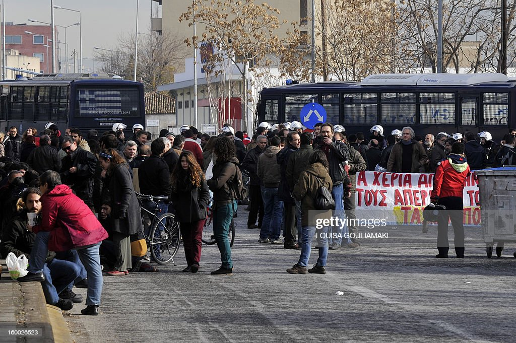 People gather by a police blockade near Athens main metro depot on January 25, 2013, after police broke out a sit-in by on-strike workers on January 25, 2013. The raid on the centre, which strikers protesting austerity measures had occupied took place overnight. The government had ordered a civil mobilisation the day before to force the Athens metro staff to halt their strike, which has disrupted traffic in the Greek capital for over a week. Unions reacted by calling a general transport standstill today.