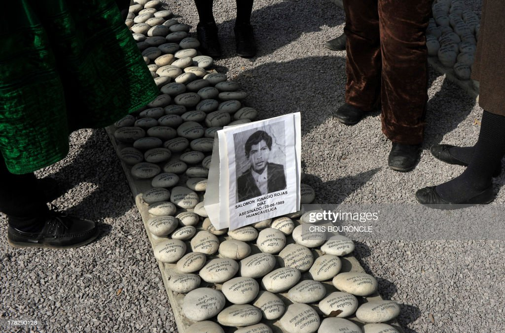 People gather by a portrait at a symbolic graveyard of stones reading names of victims of the war against terrorist groups as The Shinning Path and the Tupac Amarus during the 80's and 90's, in Lima on August 28, 2013. Relatives of victims commemorate the 10th anniversary of the release of the report of the Commission of Truth and Reconciliation of Peru, which concluded that there were 69.000 people killed or missing during the 80's and 90's.