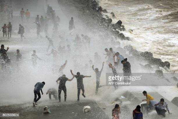 TOPSHOT People gather by the Marine Drive seafront to be hit by breaking waves at high tide in Mumbai on June 28 2017 PARANJPE