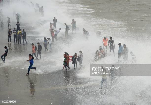 People gather by the Marine Drive seafront to be hit by breaking waves at high tide in Mumbai on June 28 2017 PARANJPE