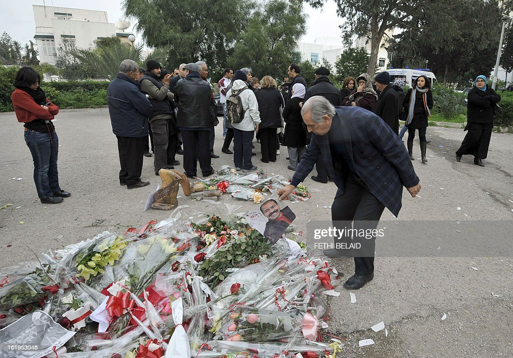 People gather close to the vandalised and broken statue of murdered opposition figure Chokri Belaid, erected in his honour, on February 18, 2013, in Tunis. The memorial, installed as a work of contemporary art by Tunisian artists, was ripped off from its base and broken, and the flowers surrounding it were trampled and scattered. Belaid, a leftist leader and fierce critic of Tunisia's ruling Islamist-led government, was shot dead by a gunman as he left his home. is seen left. AFP PHOTO / FETHI BELAID