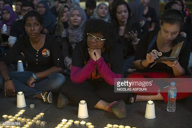 People gather during a candlelight vigil for the victims of the Malaysia Airlines flight MH17 from Amsterdam to Kuala Lumpur at a shopping mall in...
