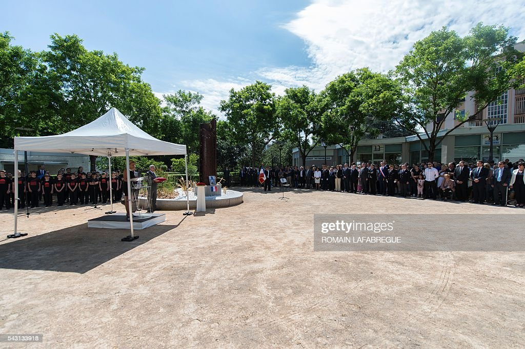 People gather during a memorial ceremony on June 26, 2016 in Fontaines-sur-Saone, where a sculpture was built on the place in tribute to Herve Cornara, killed one year ago in a terror attack at the Air Products factory in Saint-Quentin-Fallavier. In June, 2015, Yassin Salhi beheaded Herve Cornara, owner of a company where he had worked near Lyon. / AFP / ROMAIN