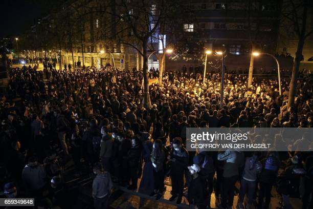 TOPSHOT People gather during a protest in front of the police headquarters in the 19th arrondissement of Paris on March 28 following the death of a...