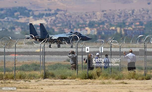 People gather for a closer look at a B2 Stealth Bomber passing by on way to take off at the Palmdale Aircraft Integration Center of Excellence in...