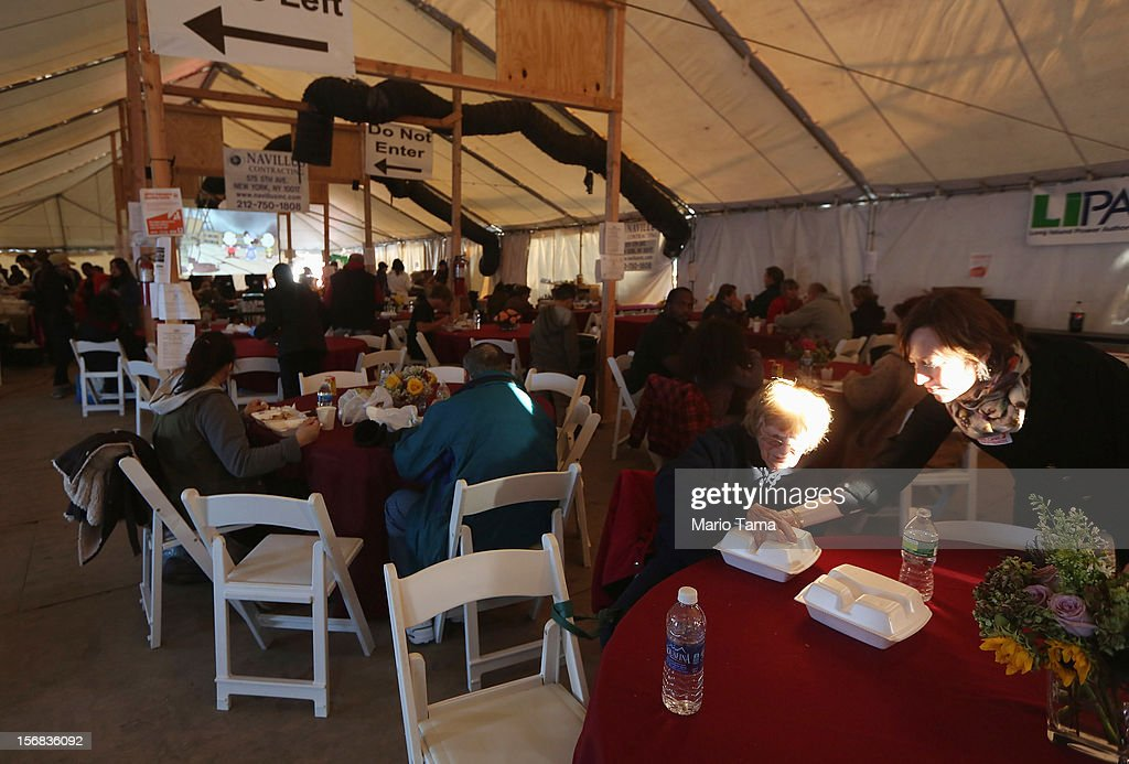 People gather for a free Thanksgiving dinner in a tent in the Rockaway neighborhood on November 22, 2012 in the Queens borough of New York City. A number of organizations are providing free Thanksgiving meals for residents of the Rockaways which was hard hit by Superstorm Sandy.