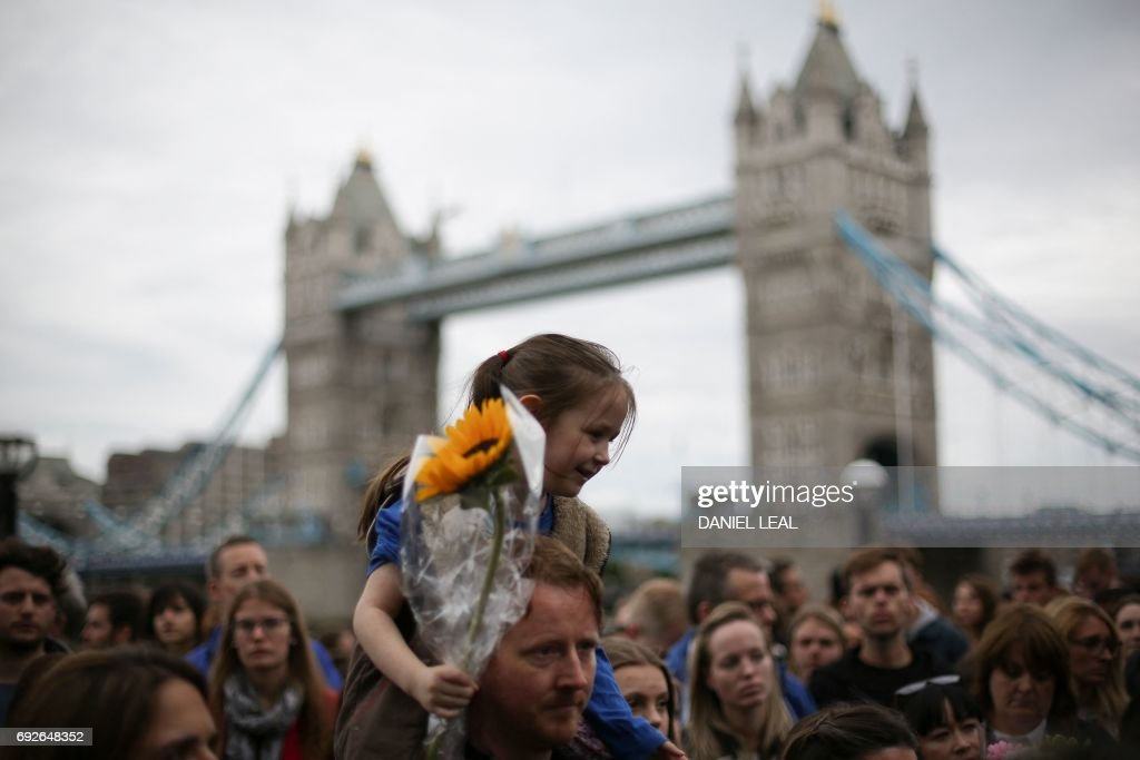 TOPSHOT - People gather for a vigil in Potters Fields Park in London on June 5, 2017 to commemorate the victims of the terror attack on London Bridge and at Borough Market that killed seven people on June 3. London police made a fresh round of arrests Monday after the country's third terror attack in less than three months as Prime Minister Theresa May came under mounting pressure over security three days ahead of elections. The aftermath of Saturday night's rampage, which left seven dead and dozens wounded, dominated the campaign trail. OLIVAS