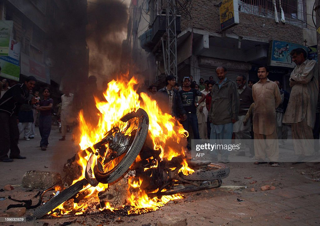 People gather in front of a burning motorbike set alight by angry protestors of the ruling Pakistan Peoples Party in Hyderabad on January 15, 2013, against the Supreme Court decision to arrest the prime minister Raja Pervez Ashraf. Pakistan's top judge Tuesday ordered the arrest of the prime minister over graft allegations, threatening to worsen turmoil as thousands of protesters demanded parliament be dissolved. AFP PHOTO/Yousuf NAGORI