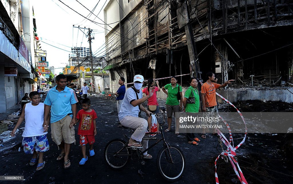 People gather in front of a burnt building on Rama 4 road in Bangkok on May 20, 2010. The top Thai protest leader urged supporters of the anti-government 'Red Shirt' movement to refrain from violence after riots in the capital, saying 'democracy cannot be built on revenge.'