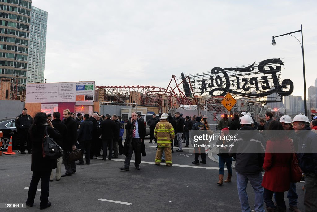 People gather in front of a construction crane after it collapsed on January 9, 2013 in the Queens borough of New York City. The crane collapse injured seven construction workers on the site in the Long Island City neighborhood.
