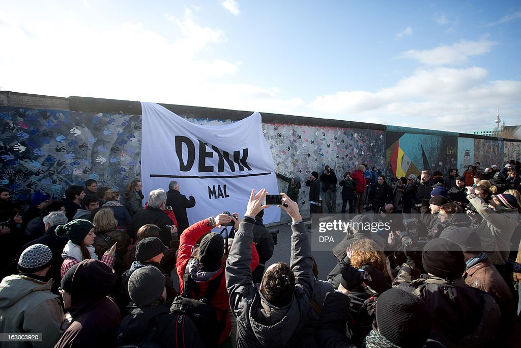 People gather in front of a giant banner reading 'Denk Mal' - a German play-on-words meaning 'Memorial' and 'Think about' hanging on the so-called East Side Gallery, the Berlin Wall's longest remaining, to demonstrate against the dismantling of a segment of the outdoor gallery in Berlin, Germany, on March 3, 2013. Detested for nearly three decades as a symbol of oppression, the Berlin Wall again sparked angry protests since a crane on March 1, 2013 began dismantling a segment under plans for a new housing development. AFP PHOTO / Jörg Carstensen +++ GERMANY