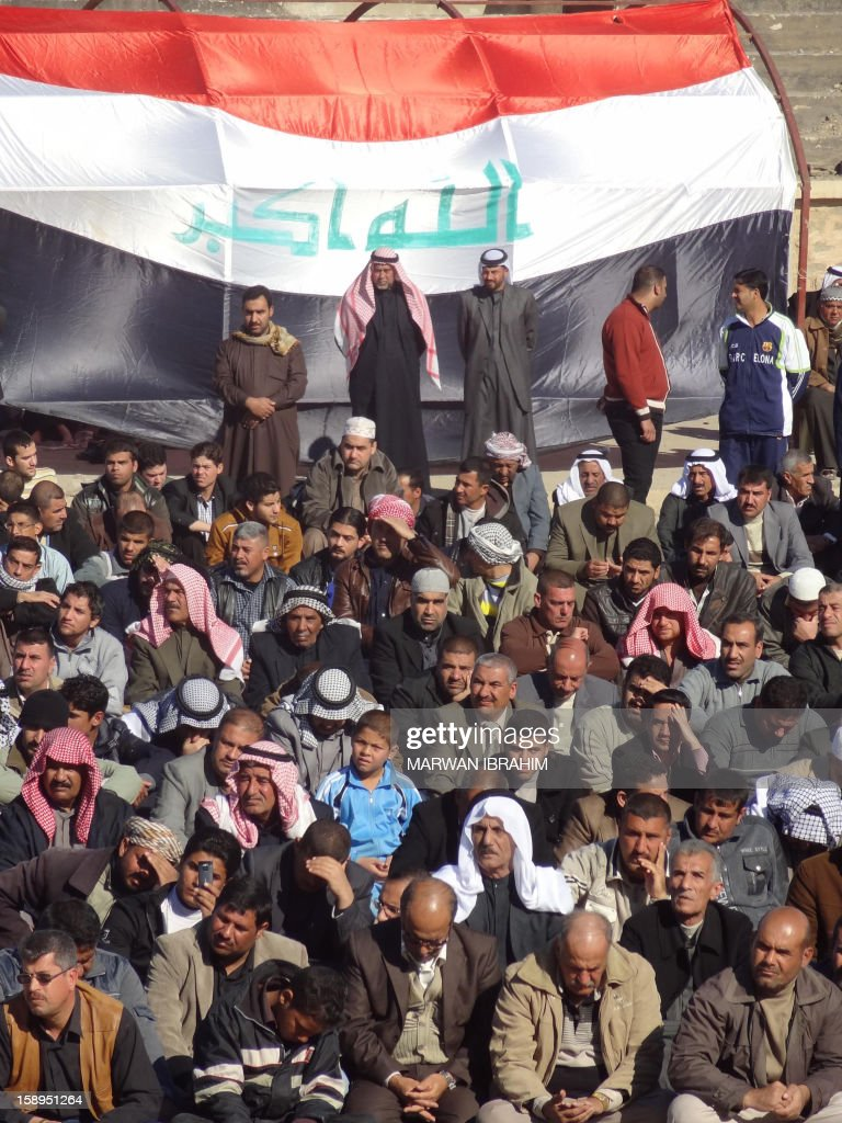 People gather in front of a giant Iraqi flag during a demonstration on January 4, 2013 in the northern Iraq's Kirkuk province as part of a national day of rallies by Sunni Muslims criticising Iraq's premier and demanding the release of prisoners they say are wrongfully held.Thousands of Sunni Muslims demonstrated also in Baghdad, in the latest of nearly two weeks of rallies.