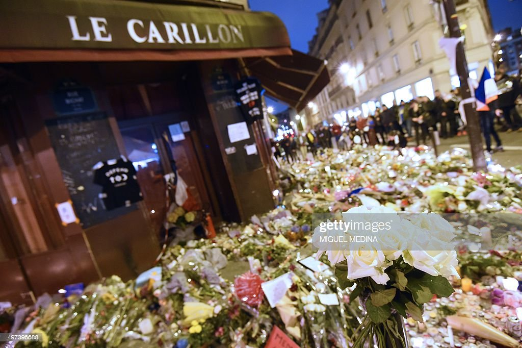 People gather in front of a makeshift memorial outside Le Carillon cafe on November 16 2015 at the corner of Rue Bichat and Alibert in the 10th...