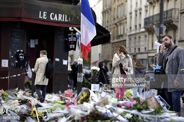 People gather in front of a makeshift memorial outside Le Carillon cafe on November 17 2015 at the corner of Rue Bichat and Alibert in the 10th...