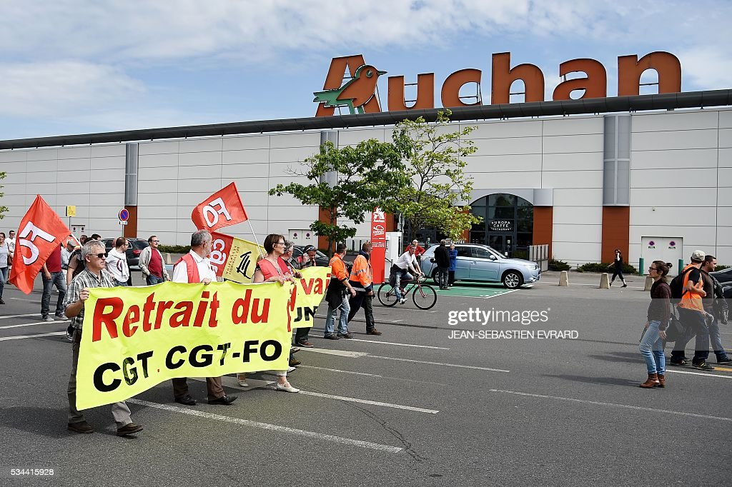 People gather in front of a supermarket in Saint-Nazaire, western France, to protest against the government's planned labour law reforms on May 26, 2016. France's Socialist government has bypassed parliament and rammed through a labour reform bill that has sparked two months of massive street protests. / AFP / JEAN