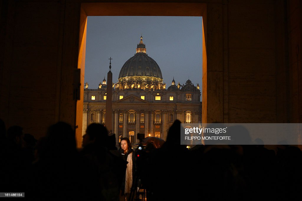 People gather in front of Saint Peter's dome at the Vatican on February 11, 2013 after Pope Benedict XVI announced he will resign as leader of the world's 1.1 billion Catholics on February 28 because his age prevented him from carrying out his duties -- an unprecedented move in the modern history of the Catholic Church.