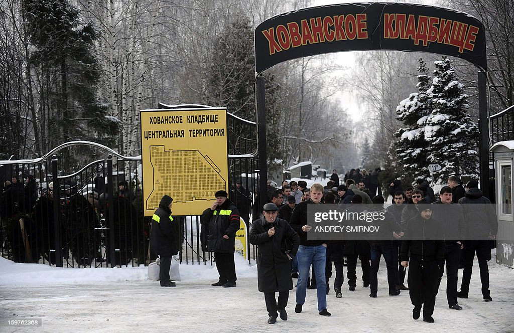 People gather in front of the entrance to Hovanskoye cemetery in Moscow on January 20, 2013. Russian crime boss Aslan Usoyan was buried in a tightly controlled ceremony in Moscow on Sunday, after efforts to fly his body to his hometown in Georgia fell through. Usoyan, 75, was the head of a gang that is reportedly the most powerful in the former Soviet Union.