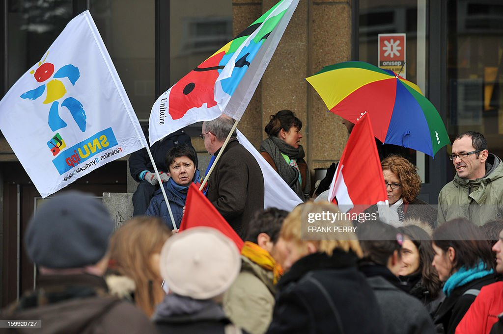 People gather in front of the headquarters of the local office of the Education department, on January 23, 2013, in Rennes, as they take part in a nationwide strike and protest action against a proposed reform to increase the class time of primary school students. Around 80 people gathered in Rennes as several hundred other teachers gathered at protest rallies in various cities across the country. AFP PHOTO / FRANK PERRY