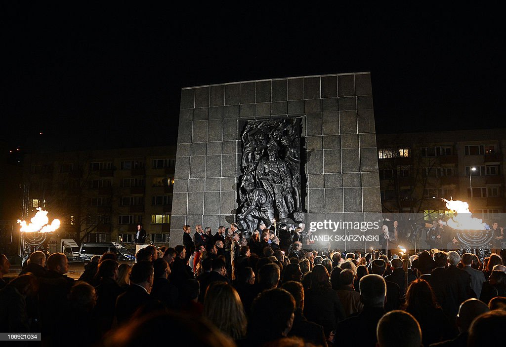 People gather in front of the monument to the fighters of the Warsaw ghetto uprising in Warsaw on April 18, 2013 for the evening commemorations on the eve of the 70th anniversary of the outbreak of the 1943 revolt.