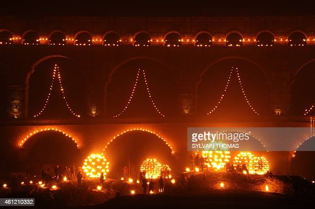 People gather in front of the Pont du Gard decorated with lights during the 'Nuit des Lucioles' an event to celebrate the 30th anniversary of the...