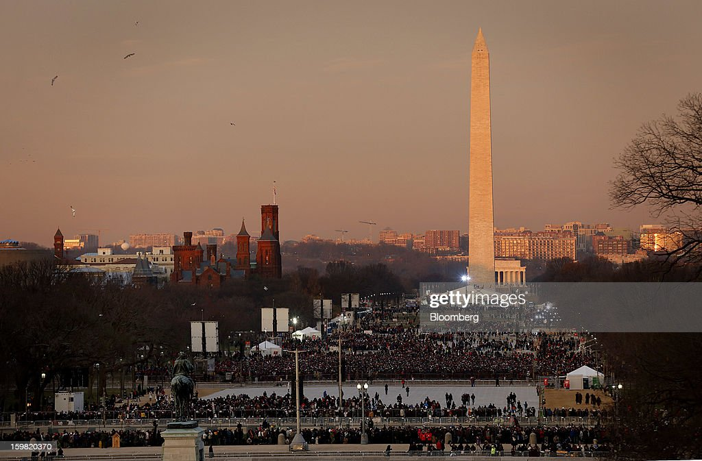 People gather in front of the Washington monument before the start of the U.S. presidential inauguration in Washington, D.C., U.S., on Monday, Jan. 21, 2013. As he enters his second term President Barack Obama has shed the aura of a hopeful consensus builder determined to break partisan gridlock and adopted a more confrontational stance with Republicans. Photographer: Joshua Roberts/Bloomberg via Getty Images