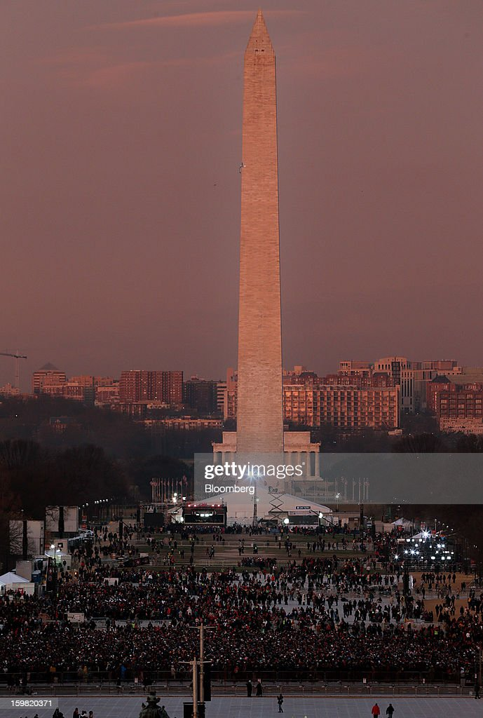 People gather in front of the Washington monument before the start of the U.S. presidential inauguration in Washington, D.C., U.S., on Monday, Jan. 21, 2013. As he enters his second term President Barack Obama has shed the aura of a hopeful consensus builder determined to break partisan gridlock and adopted a more confrontational stance with Republicans. Photographer: Scott Eells/Bloomberg via Getty Images