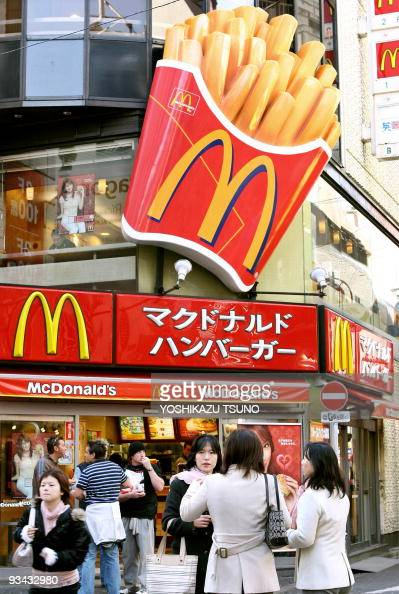 People gather in front of US restaurant giant McDonald's in Tokyo 10 February 2006 Japan's McDonald's Holdings announced the company net profit last...