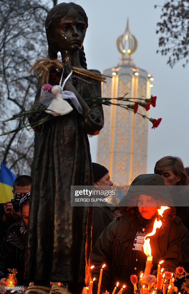 People gather in memory of the victims of the Holodomor famine during a ceremony at the Holodomor memorial in Kiev on November 24, 2012. Ukraine marked 80 years since the Stalin-era Holodomor famine, one of the darkest pages in its entire history that left millions dead and which is regarded by many as a genocide. The 1932-33 famine took place as harvests dwindled and Josef Stalin's Soviet police enforced the brutal policy of collectivising agriculture by requisitioning grain and other foodstuffs. AFP PHOTO/ SERGEI SUPINSKY