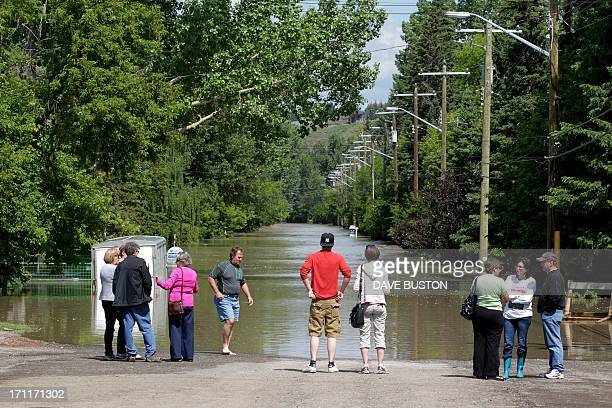 People gather in the Bowness neighbourhood looking down a waterfilled street near the flooded Bow River in Calgary Alberta Canada June 22 2013 Water...