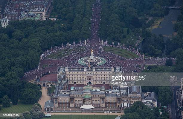 People gather in the Mall to watch a fly past over Buckingham Palace as part of Her Majesty The Queen's Birthday Flypast during Trooping the Colour...