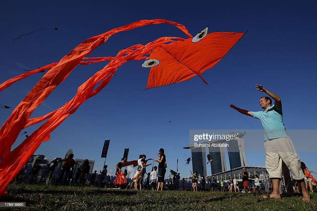 People gather in the park to fly kites during the Singapore Kite Festival at the Promontory at Marina Bay on August 31, 2013 in Singapore. Into its fifth edition, the annual two day festival attracts hundreds of kite enthusiast who spend the days flying kites in various locations around Marina Bay.
