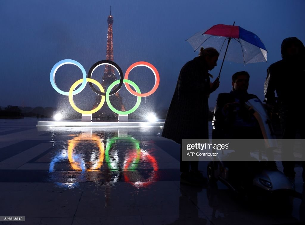 People gather in the rain beside the Olympics Rings on the Trocadero Esplanade near the Eiffel Tower in Paris, on September 13, 2017, after the International Olympic Committee named Paris host city of the 2024 Summer Olympic Games. The International Olympic Committee named Paris and Los Angeles as hosts for the 2024 and 2028 Olympics on September 13, 2017, crowning two cities at the same time in a historic first for the embattled sports body. /