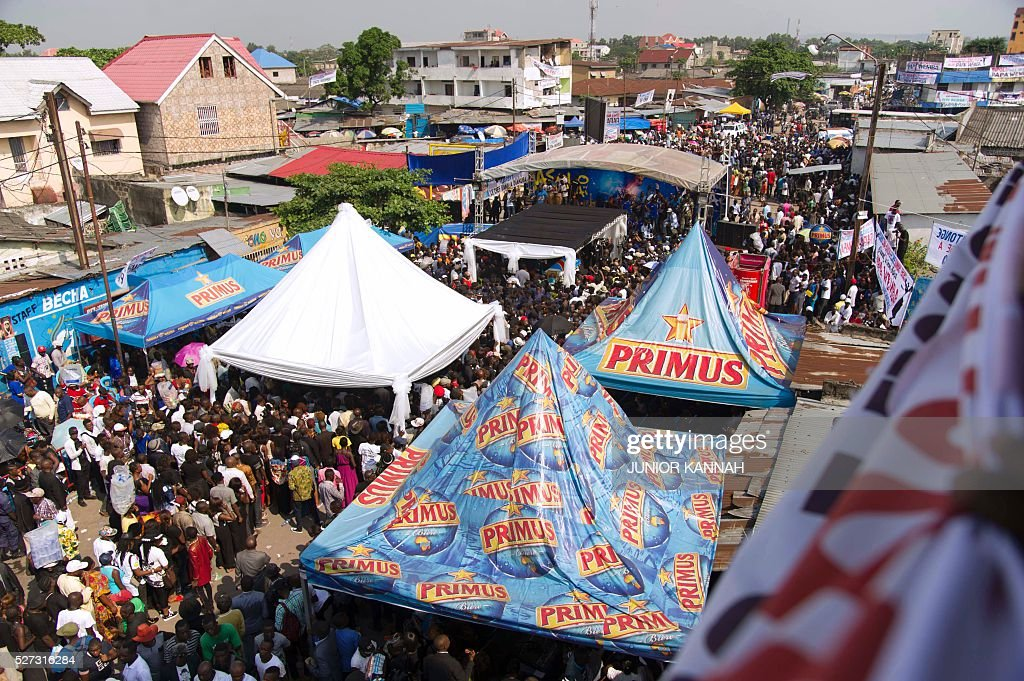 People gather in the streets of 'Village Molokoi', in the Matonge neighborhood of Kinshasa, to pay tribute to late rumba musician Papa Wemba on May 2, 2016. Democratic Republic of Congo's rumba king Papa Wemba was posthumously awarded one of his country's highest honours, a week after he collapsed on stage and died aged 66. / AFP / JUNIOR