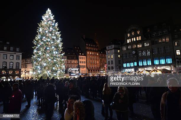 People gather near a Christmas tree in Strasbourg eastern France on November 28 on the opening day of the city's Christmas market the largest and one...