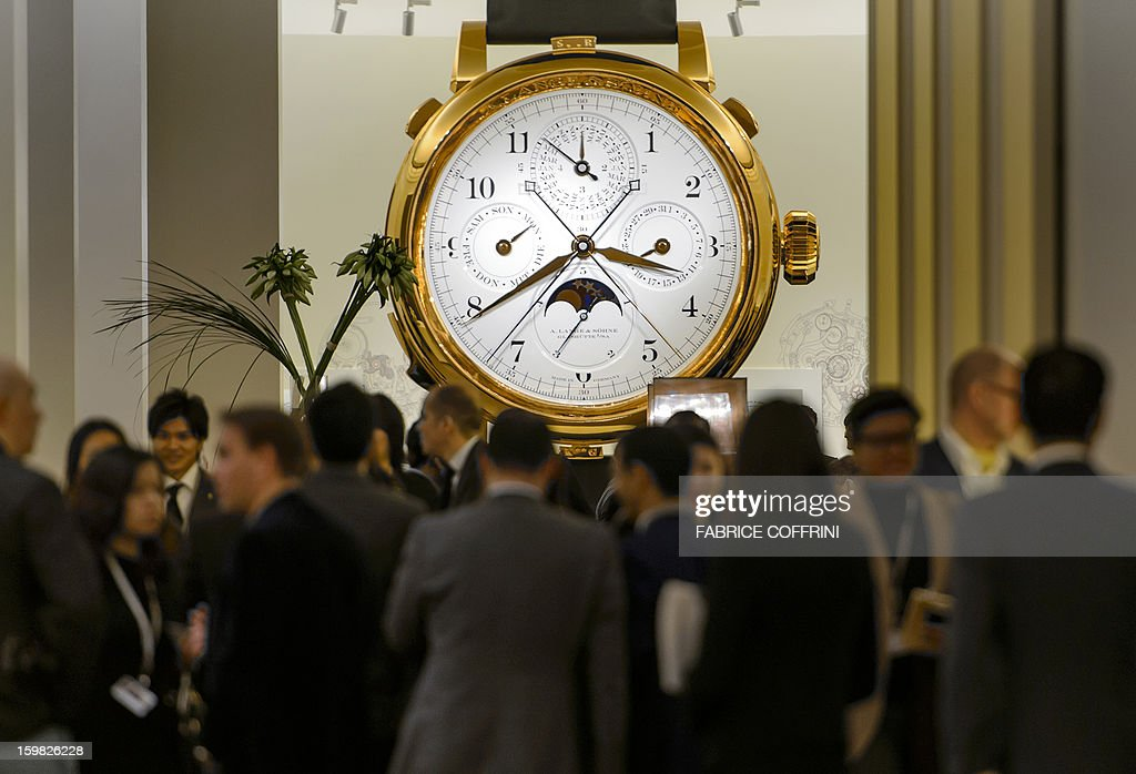 People gather near a giant model watch by watchmaker 'A. Lange & Soehne', part of luxury goods group Richemont, during the opening day of the 'Salon International de la Haute Horlogerie' (SIHH), a professional fair in fine watchmaking, on January 21, 2013, in Geneva. Swiss manufacturer of luxury goods Richemont announced that sales met expectations for the third quarter of its 2012 fiscal year at 2.8 billion Euros, up 5% from the preceding year at the constant exchange rate and 9% at the real exchange rate.