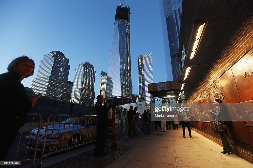 People gather near a memorial to firefighters in Lower Manhattan as One World Trade Center (TOP C) rises under construction on October 22, 2012 in New York City. The Census Bureau reported last month that between 2000 and 2010 the downtown population grew by nearly 40,000 people, in spite of the September 11 terrorist attacks at the World Trade Center. One World Trade Center is scheduled to open in 2014 at the symbolic height of 1,776 feet and will be the tallest building in the Western Hemisphere.