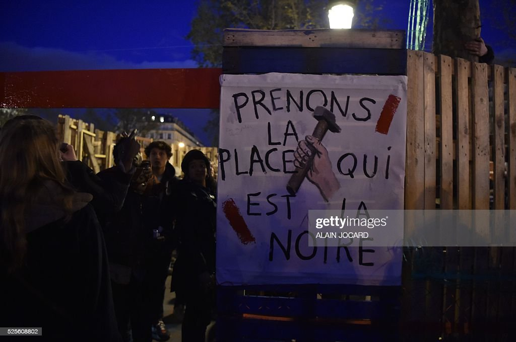 People gather near a placard reading 'Let's take the space that's ours' on Place de la Republique during the Nuit Debout, or 'Up All Night' movement on April 28, 2016 in Paris. The 'Nuit Debout' demonstrations began on March 31 in opposition to the government's proposed labour reforms.