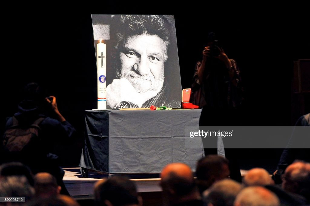 People gather near a portrait of late Bosnian Croat war criminal Slobodan Praljak, who commited suicide by drinking poison in front of UN judges, during a commemoration ceremony in Zagreb on December 11, 2017. Some 2,000 people packed a public memorial in Zagreb on December 11 for Praljak, who swallowed potassium cyanide during a hearing at the International Criminal Tribunal for the former Yugoslavia (ICTY) broadcast live around the world on November 29, 2017.