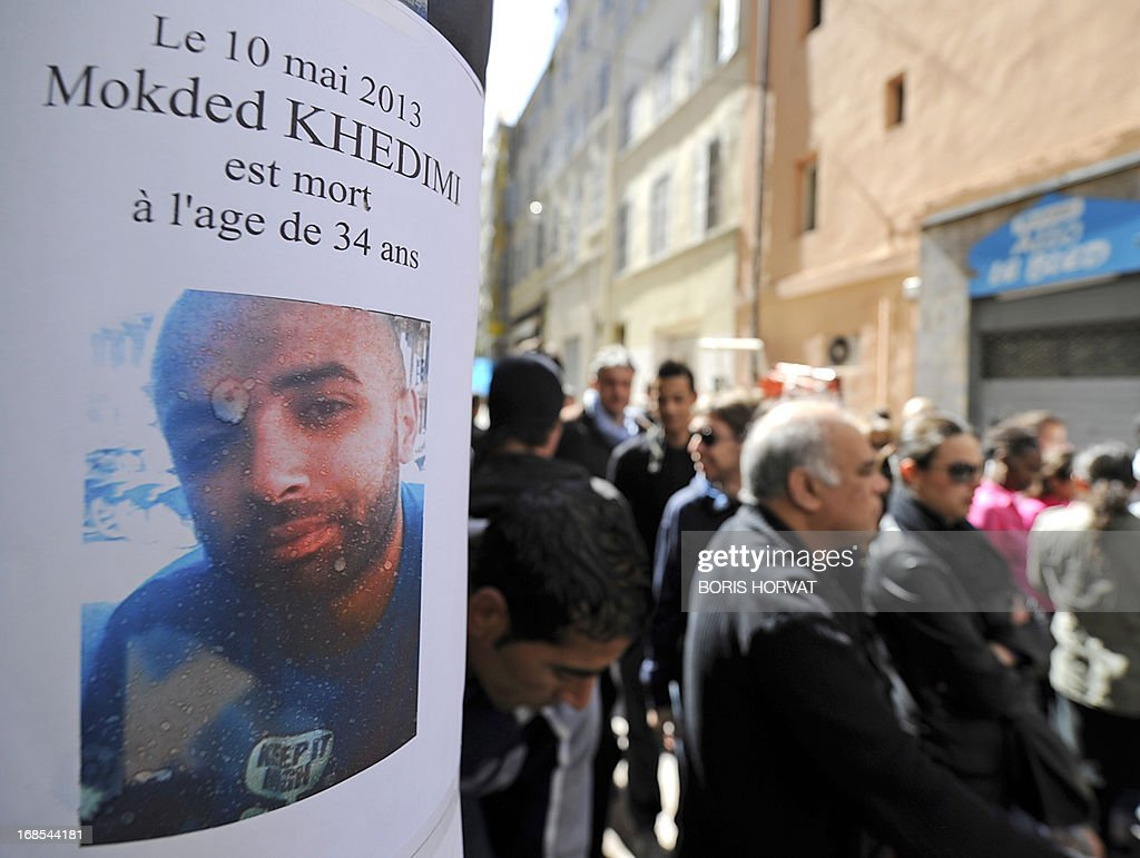 People gather near a sign reading 'Mokded Khedimi died May 10, 2013 at the age of 34' during a silent march in Marseille on May 11, 2013 in memory of Khedimi, who died after sustaining fatal injuries during a brawl on May 9. According to French police, two brothers are being actively sought.